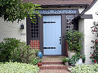 Light blue front dorr with plants around it