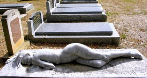 Figure of nude female on top of tombstone